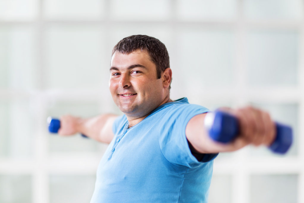Uomo sovrappeso che solleva pesi