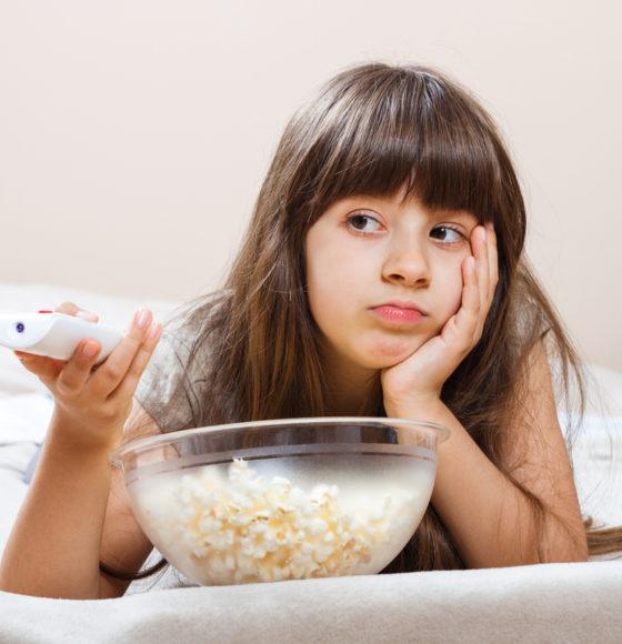 Bambina annoiata mangia popcon