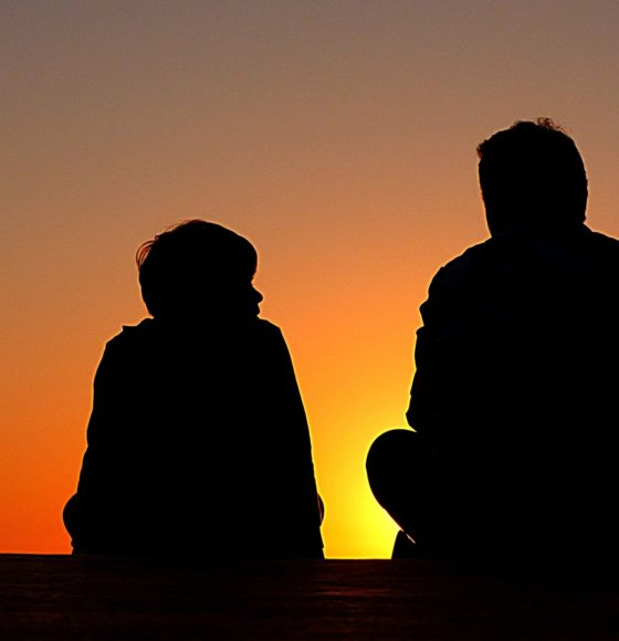 dad and son silhouette on sunset